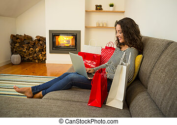 Online shopping - Beautiful woman at home at the warmth of...
