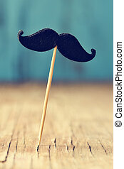 felt mustache in stick on a wooden surface - a felt mustache...