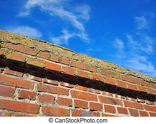 Bottom view on a fragment of red brick fence against a...