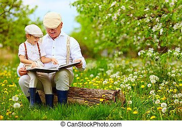 grandfather reading a book to his grandson, in blooming...