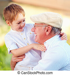 portrait of happy grandpa and grandson having fun outdoors
