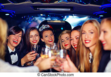 group of happy elegant women clinking glasses in limousine,...