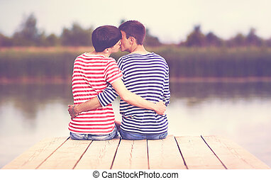 male couple, kissing, while sitting on wooden pier at...