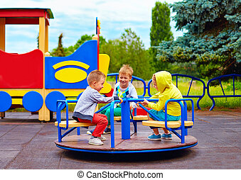 three little friends, kids having fun on roundabout at...