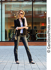 Young business woman walking on the city street
