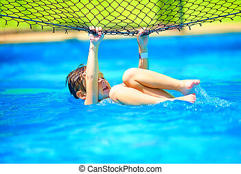 cute boy kid having fun, making stunt on volleyball net in...