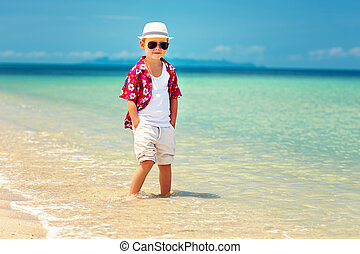 cute fashionable boy stands in surf on summer beach