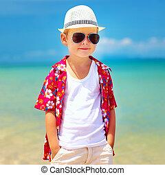 cute fashionable boy walking on summer beach