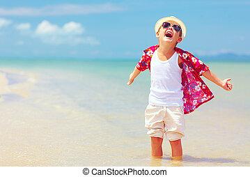 happy fashionable kid boy enjoys life on summer beach