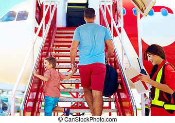 family are boarding on airplane, female steward welcomes...