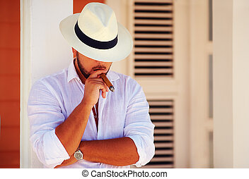 confident handsome man smoking cigar, while leaning on the...