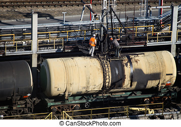 Railway oil terminal - Two workers inspect oil on rail tank...