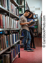 Students reading book in library - Portrait of a young...