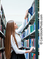 Woman searching book in university library - Portrait of a...