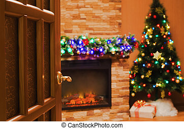 room with an electric fireplace and a Christmas tree - The...