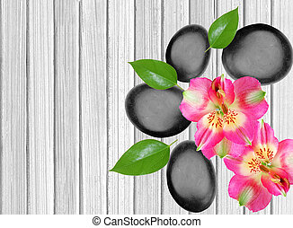 Black spa stones and pink orchid on white wooden background