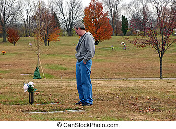 cemetery - man in autumn cemetery paying his respects