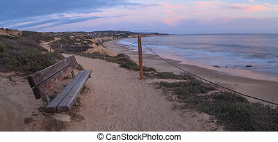 Bench at sunset along an outlook with a view of Crystal Cove...