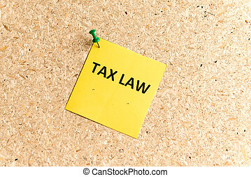 tax law word typed on a paper and pinned to a cork notice...