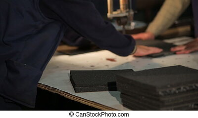 two workers cut polyurethane foam - production of components...