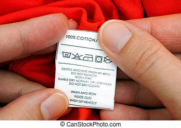 Womans hands holding clothes label 100 cotton Cleaning...