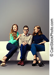 shy man - A shy young man sitting on the couch with two...