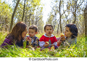 two mothers with their kids eating apples in the forest