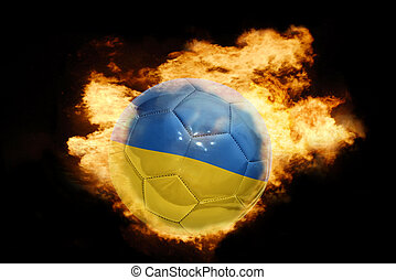 football ball with the flag of ukraine on fire - football...