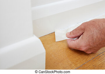 Close Up Of Man Removing Masking Tape From Skirting Board