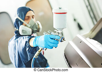 worker painting auto car bumper - Close-up of spray gun...