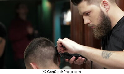 Young stylish tattooed barber cutting hair of a young man at...