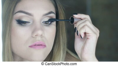 Video of woman applying makeup - Video of an attractive...