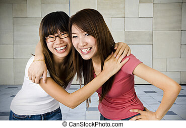 Happy Student - Two young Asian university students in...