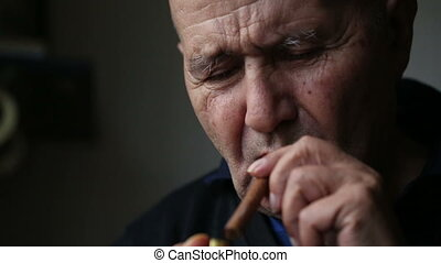 Old man smoking a cigar. - Old man smoking a cigar front...