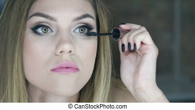 Video of a woman applying mascara - Video of an attractive...