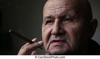Old man smoking a cigar.