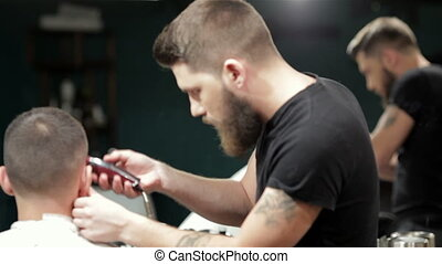 Barber cutting bearded brutal man, reflection in the mirror