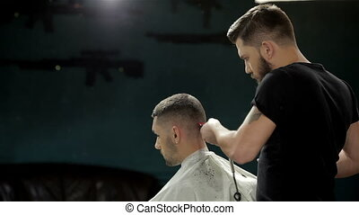 Young man having a haircut with a hair clippers - Men's...