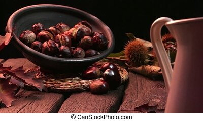 Roasted chestnuts and leaves - Roasted chestnuts on a rustic...