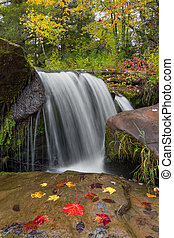 Autumn Plunge - Whitewater plunges over a rock ledge with...