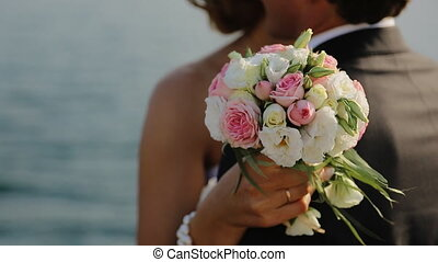 Groom and bride together. Wedding couple. the couple standing together in the hands of the bride's beautiful and delicate bouquet of delicate flowers. on the pier near the water and embrace, in the background we see the water