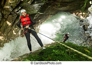 Team Of Mixed People On Canyoning Adventure - Rappelling...