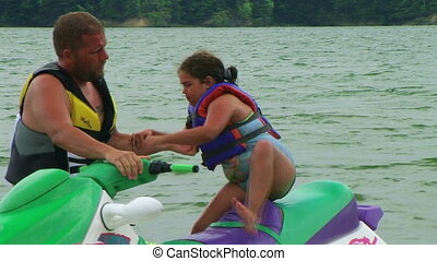 Daughter Getting Off Jet Ski - Father helps daughter get off...