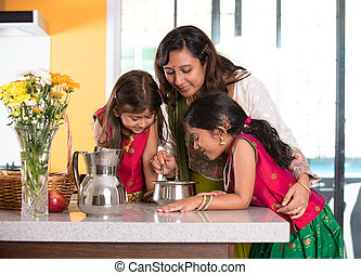 indian mother cooking with her daughters at kitchen