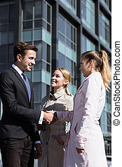 Young corporate employees standing near corporate building