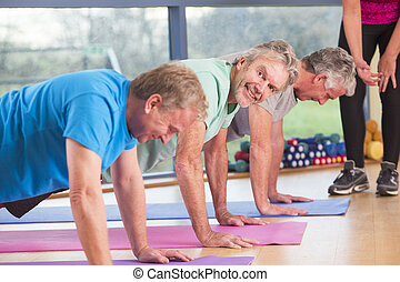 Three men doing press-ups at the gym - Three senior men...