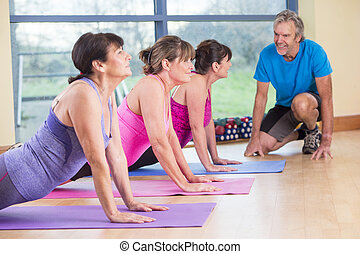 Three women stretching at the gym
