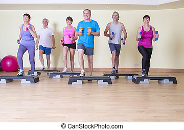 Senior steps class with weights at the gym