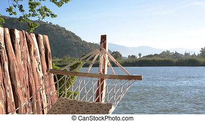 Empty hammock on the wooden pier near the water