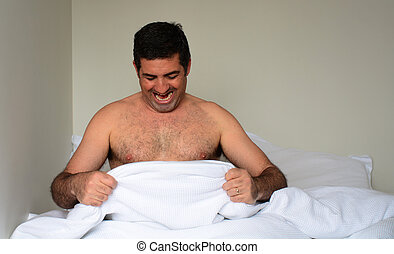 Happy man in his forties (40s) in bed looking down at his...